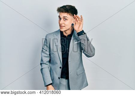 Young caucasian boy with ears dilation wearing business jacket smiling with hand over ear listening an hearing to rumor or gossip. deafness concept.