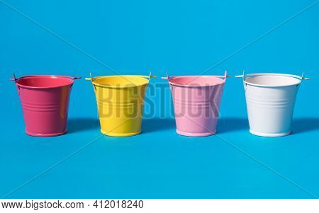 Four Multi-colored Buckets On A Blue Background. Small Buckets Red Yellow Pink White. Farming Or Rep