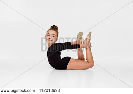 Young Beautiful Gymnast Girl In Black Sportswear Performs Gymnastic Poses