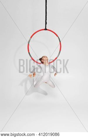 Graceful Child Girl Gymnast In White Sportwear Shows An Acrobatic Performance On An Aerial Hoop. Acr