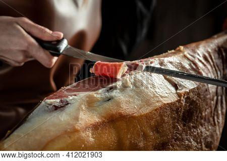 Butcher Cuts Jamon With Knife. Iberian Ham Cutter. Dry Spanish Ham, Jamon Serrano, Bellota, Italian