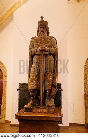 Stone Carved Statue Of A King With A Sword In His Hands And A Crown On His Head, Medieval Monument,