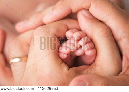 Loving Parent Hold Babys Legs. Happy Childhood. Parental Care. Concept Of A Happy Family.