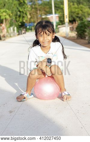 Asian Little Girl Sits Resting On The Ball After Playing With A Full Sweat On My Face In The Hot Sun