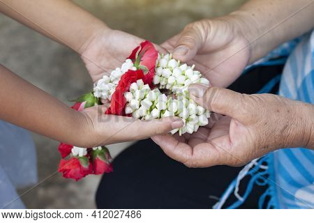 The Daughter Holds A Garland To Pay Her Mother With Love And Respect On Mother's Day In Thailand Or