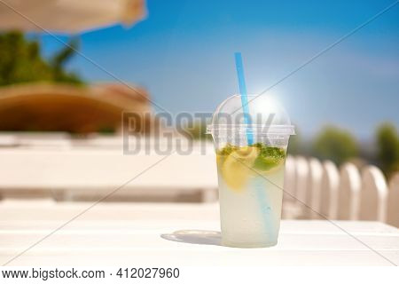 Ice Invigoration Summer Drink On Wooden Table On Open Terrace. Concept Cool Refreshing Lemonade For