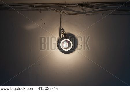 An Incandescent Light Bulb With Cobwebs And Dirt Illuminates The White Wall In The Entrance Of The H