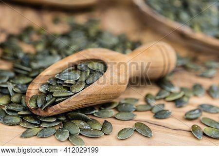 A Pile Of Roasted Pumpkin Seeds On Olive Wood