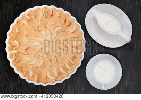 Home Baking Of Ripe Apples On A Dark Wooden Background. Fruit Cake In A Dish And Cream. Big Apple Pi