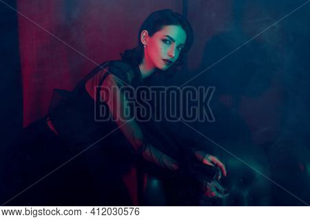 Beautiful brunette girl in fashionable black dress sits in a leather armchair in a luxury apartment. Beauty, fashion chic concept. Glamorous lifestyle.