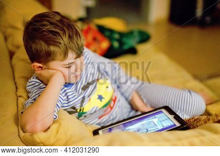 Little School Kid Boy Making Homework With Tablet. Schoolchild Reading And Learning With Computer, S