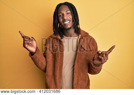 African american man with braids wearing brown retro jacket smiling confident pointing with fingers to different directions. copy space for advertisement