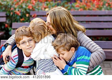 Mother And Three Children Hugging. Happy Family Sitting Outdoor: Woman And Two Brother Kids Boys And