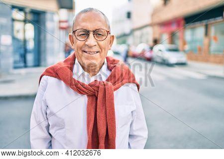 Senior man smiling happy wearing glasses walking at the city.