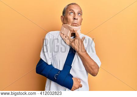 Handsome mature senior man wearing cervical collar and arm on sling thinking concentrated about doubt with finger on chin and looking up wondering