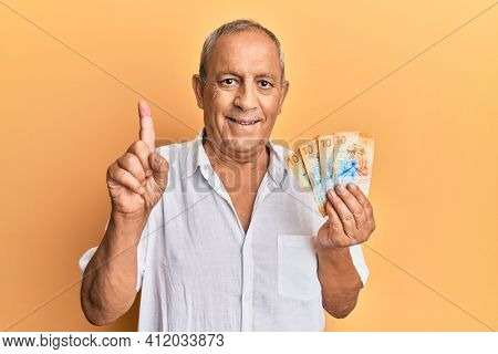 Handsome mature man holding swiss franc banknotes smiling with an idea or question pointing finger with happy face, number one