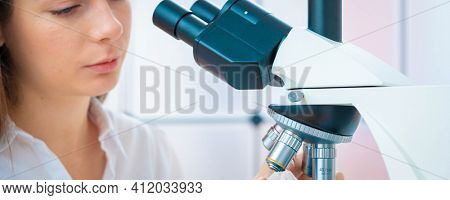 Scientist analyzing microscope slide at laboratory. Young woman technician is examining a histological sample, a biopsy in the laboratory of cancer research