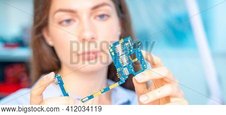 Young woman in inspection electronics PCB devise. Modern electronics laboratory