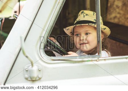 Little Girl In A Hat Sits Behind The Wheel Of An Old Disassembled Car