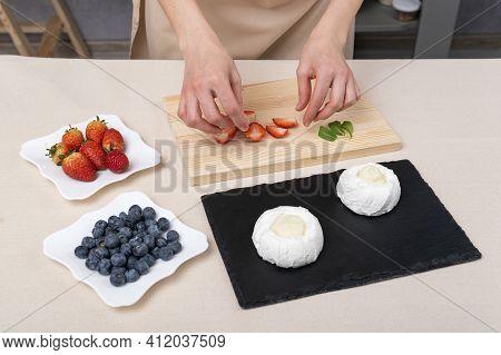 Woman Prepares Cakes Using Strawberries, Blueberries And Meringue. Cake Anna Pavlova.