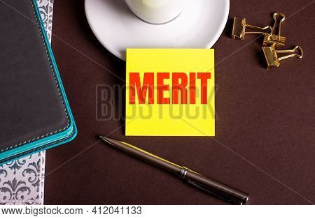 The Word Merit Written On Yellow Paper On A Brown Background Near A Coffee Cup And Diaries