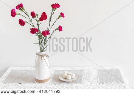 On The Table In A Ceramic Vase Are Red Carnations, Next To A Plate Of Sweets. White Background, Scan