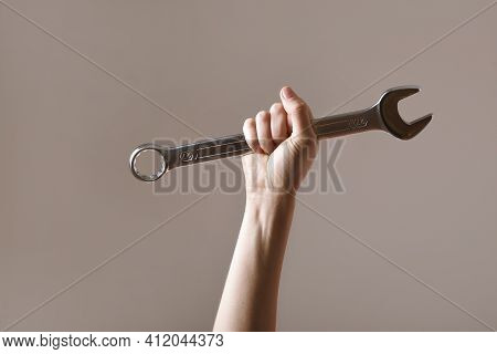 Big Spanner In The Woman's Hand. Hand Holds A Wrench On A Gray Background. Combination Wrench. Big C