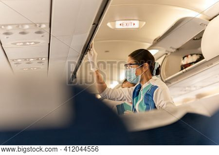Flight Attendant In Protective Masks And Glove Closing Overhead Compartment.