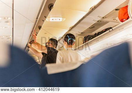 Flight Atttendant Attendant Helping Passenger To Put Luggage Cabin Compartment.