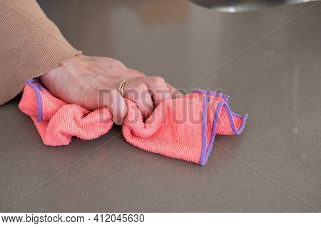 Close Up Of A Woman's Hands Wiping A Kitchen Counter Top With A Colorful Rag.cleaning And Hygiene Co