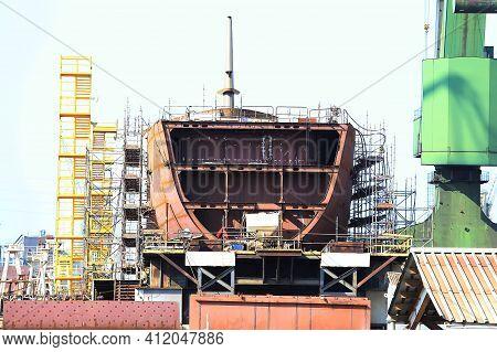 Hull Of A Large Sea Ship Under Construction At A Shipyard