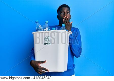 Young african american man holding recycling wastebasket with plastic bottles covering mouth with hand, shocked and afraid for mistake. surprised expression