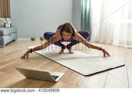Sports Coach Looking At Laptop While Doing Online Workout. Girl Trainer Conducting Online Workout At