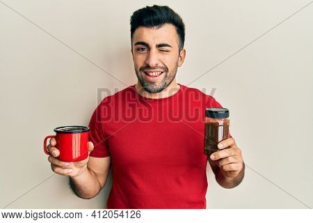 Young hispanic man holding cup of soluble coffee winking looking at the camera with sexy expression, cheerful and happy face.
