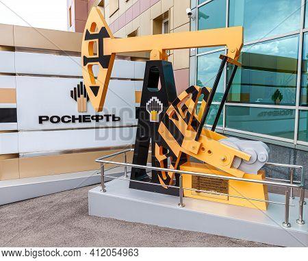 Samara, Russia - May 8, 2016: Oil Industry Equipment. Model Of Oil Pump Jack Near The Office Buildin