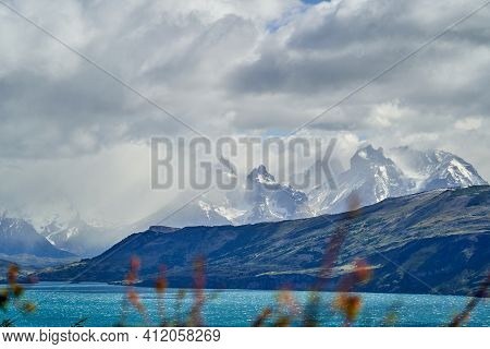 Horns Of Torres Del Paine Towering Over The Turquoise Water Of Lake Pehoe And A Mountain Ridge With