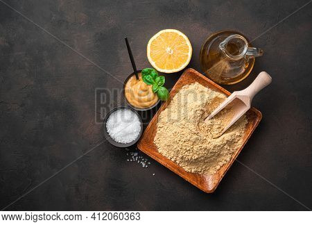 Mustard Powder And Mustard Paste With Lemon And Salt On A Brown Background. Top View With Copy Space