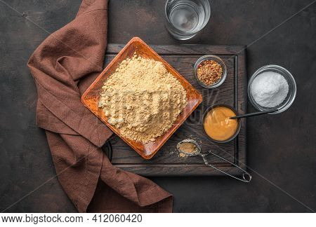 Ready-made Mustard And Mustard Powder, Spices, Salt And Water On A Cutting Board On A Brown Backgrou