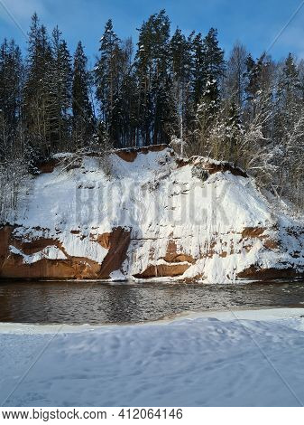 Snow-covered Cliff Along Which Flows A Small Forest River. Green Trees And Blue Sky Above The Cliff.