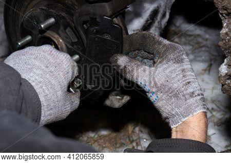 Man Mechanic Technician Worker Installing Car Wheel Maintenance In Auto Service. Hand Of Mechanic Ma