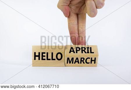 Symbol For The Change From March To April. Businessman Turns Wooden Cubes And Changes Words 'hello M