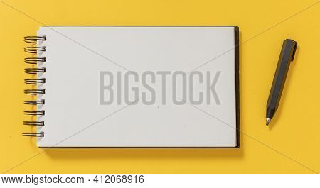 Blank Notepad And Architect Engineer Pencil On Yellow Color Background, Top View.