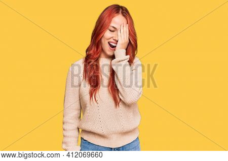 Young redhead woman wearing casual winter sweater yawning tired covering half face, eye and mouth with hand. face hurts in pain.