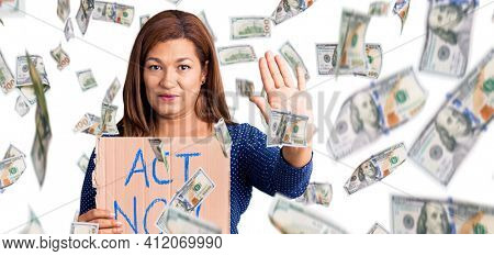 Middle age latin woman holding act now banner with open hand doing stop sign with serious and confident expression, defense gesture