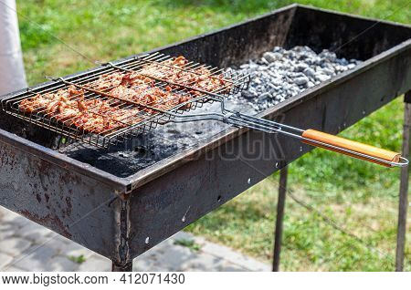 Grilled Appetizing Kebab Cooking On Metal Skewers. Shashlik During Of Cooking On The Mangal Over Hot
