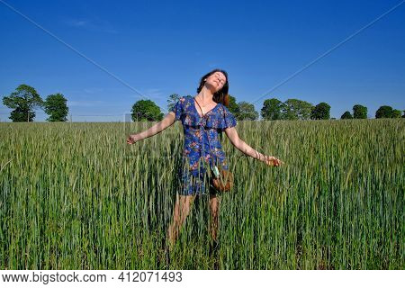 Young French Woman With A Blue Dress Enjoying The Sun And The Countryside