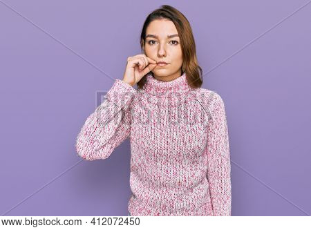 Young caucasian girl wearing wool winter sweater mouth and lips shut as zip with fingers. secret and silent, taboo talking