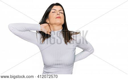 Beautiful brunette woman wearing casual clothes suffering of neck ache injury, touching neck with hand, muscular pain
