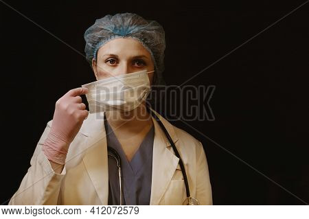 Doctor With Tired Eyes And Facial Wounds From A Medical Mask, Close-up. Nurse On A Black Background