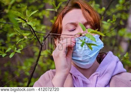 A Woman In A Medical Mask In Spring Near A Tree With Green Leaves. Concept Of Ending The Coronavirus